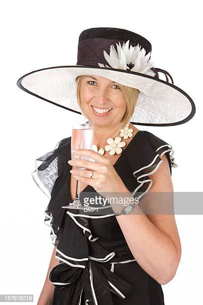 Fashionably dressed woman in hat holding glass of pink champagne