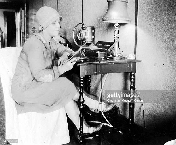 A fashionably dressed woman leans over the microphone to read a radio broadcast Cincinnati Ohio ca1920s