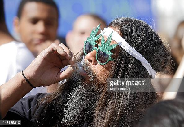 Fast Eddy Aki'a of Hawaii smokes a joint as thousands gathered to celebrate the state's medicinal marijuana laws and collectively light up at 420 pm...
