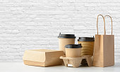 Fast food packaging set. Paper coffee cups in holder, food box, brown paper bag on the table