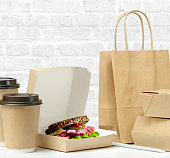 Brown box with sandwich. Fast food packaging. Paper coffee cups, brown paper bag on the table on white brick wall background