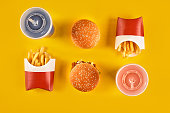 Fast food and unhealthy eating concept - close up of fast food snacks and cold drink on yellow background. Top view. Copy space. Still life. Flat lay.