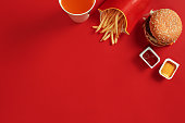 Fast food dish top view. Meat burger, potato chips and glass of drink on red background. Takeaway composition. Wrapped French fries, hamburger, mayonnaise and ketchup sauces on red desk. Copy space