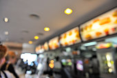 Blurred background: fast-food restaurant interior.