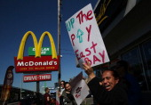 Fast food workers and activists protest outside of a McDonald's restaurant on March 18 2014 in Oakland California Dozens of fast food workers and...