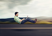 Fast internet concept. Autonomous self driving vehicle car technology. Levitating business man on road using laptop