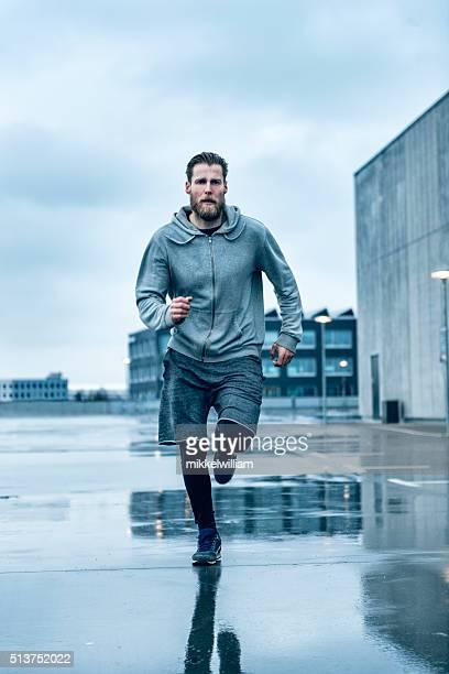Fast male runner runs outside in the rain
