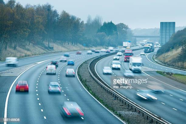Fast traffic on foggy motorway