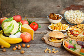 Fastfood and healthy food on old wooden background. Concept choosing correct nutrition or of junk eating.