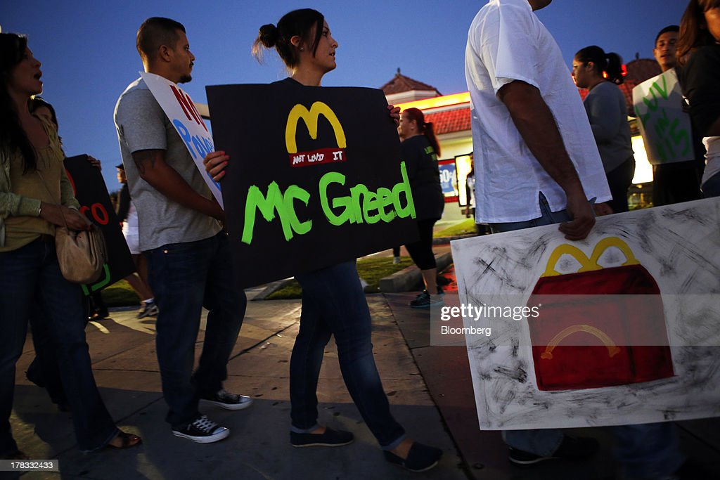 Fast-food workers and supporters organized by the Service Employees International Union (SEIU) protest for a $15 per hour wage outside of a Burger King restaurant in Los Angeles, California, U.S., on Thursday, Aug. 29, 2013. Fast-food workers in 50 U.S. cities plan to walk off the job today, ratcheting up pressure on the industry to raise wages and demanding the right to wages of $15 an hour, more than double the federal minimum of $7.25. Photographer: Patrick T. Fallon/Bloomberg via Getty Images