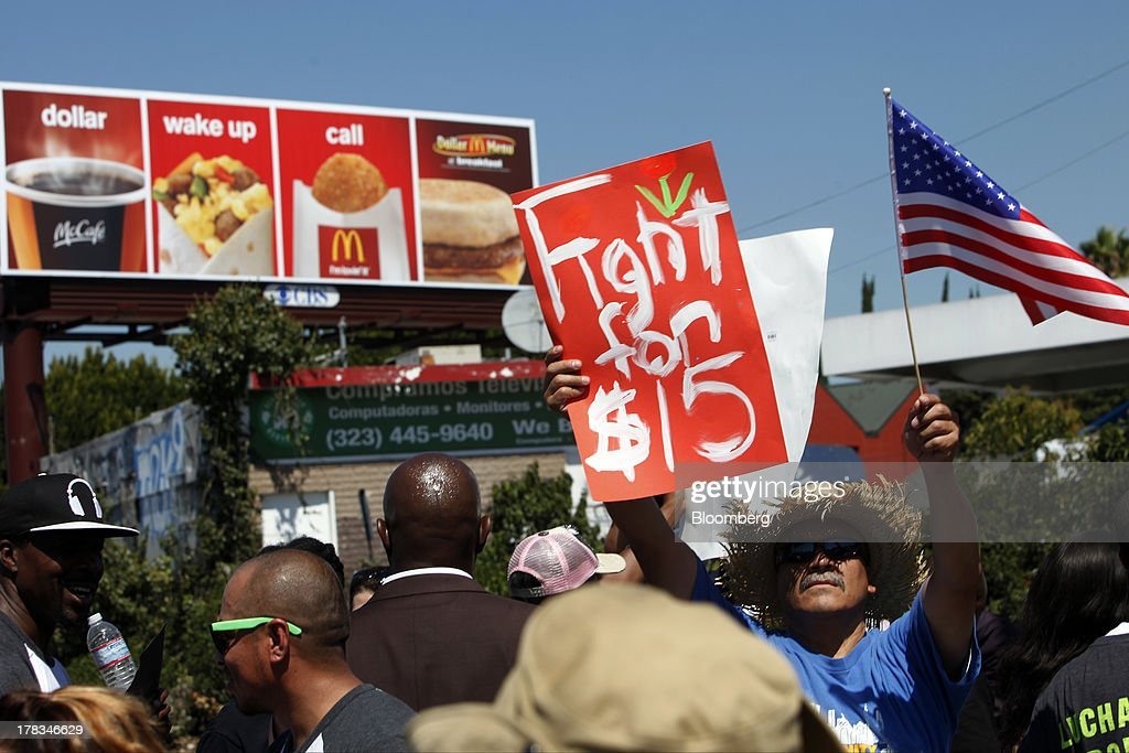 Fastfood workers and supporters organized by the Service Employees International Union protest in front of a McDonald's Corp billboard on the street...
