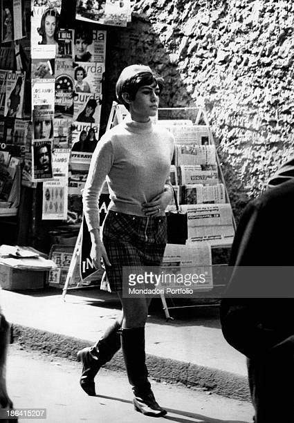A fastpaced young Argentinian woman walking along the street and behind her can be seen newspapers and magazines out of a newsstand the woman wears a...
