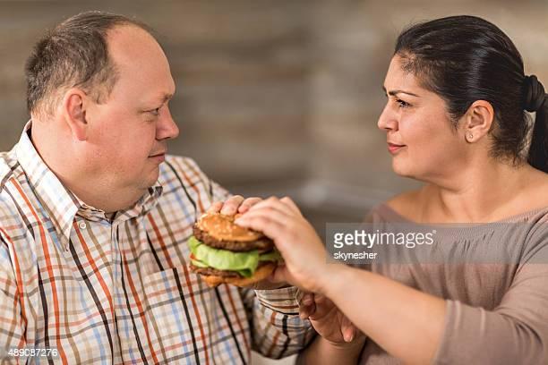 Fat couple fighting over hamburger.