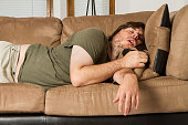 Fat guy sleeping on the couch in what looks like an uncomfortable position