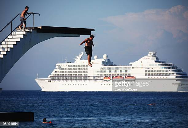 A fat kid is jumping from a diving platform into the aegean sea while a cruise ship is crossing on July 16 2009 in Rhodes Greece Rhodes is the...