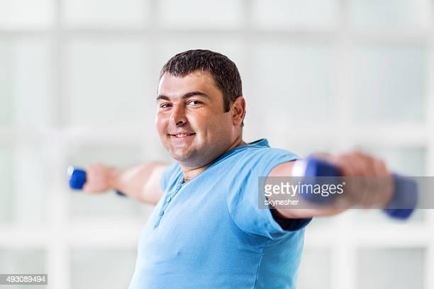 Uomo grasso esercitando con manubri e guarda alla macchina fotografica.