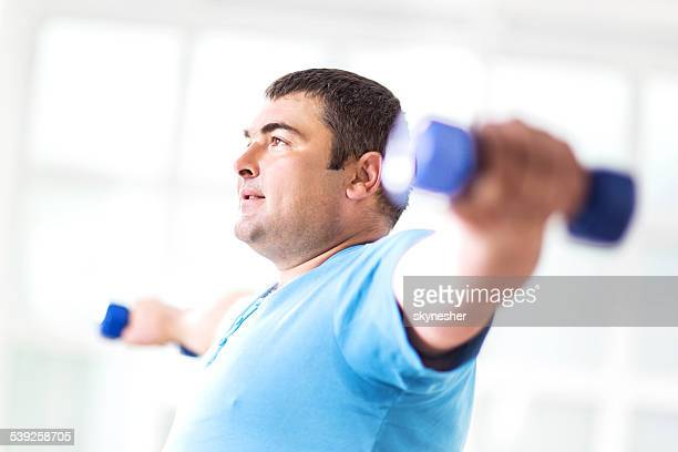 Fat man exercising with dumbbells.