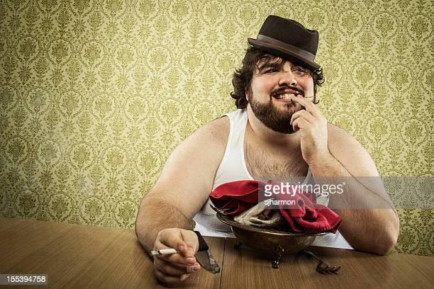 Gros homme aboutissement manger la soupe de poisson de la tête sur une table en bois