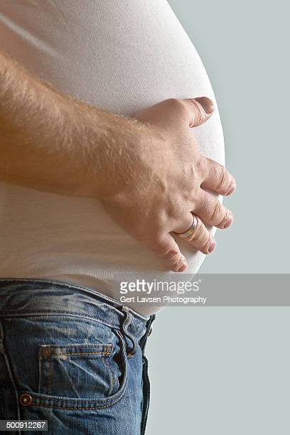 Fat man in jeans with hand on belly