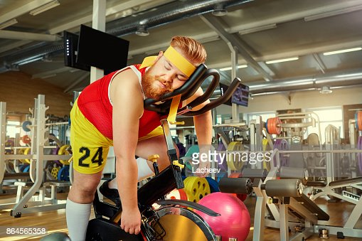 A fat man is tired on a simulator in the gym : Foto de stock