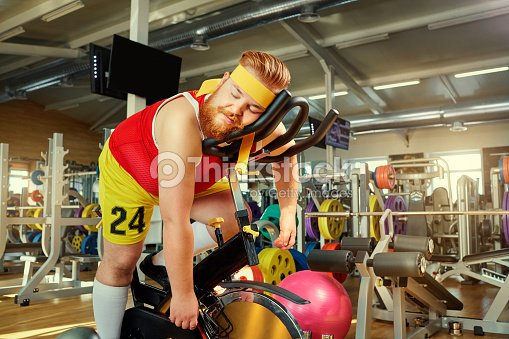 A fat man is tired on a simulator in the gym : Stock Photo