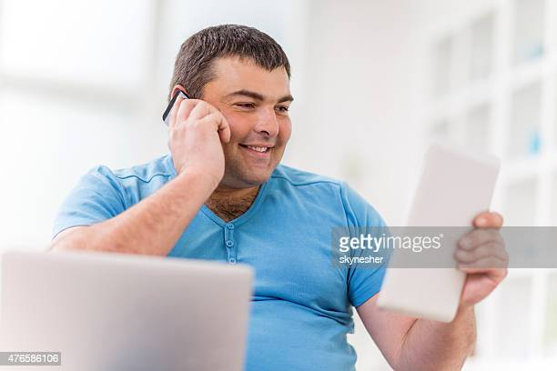 Fat man smiling and using wireless technology.