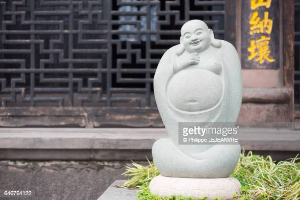 fat smiling buddha statue against traditional chinese wall