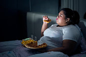 Fat woman eating pizza on bed while watching movie before sleep