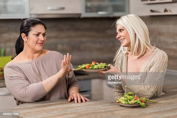 Fat woman refusant salade saine forme à son ami.