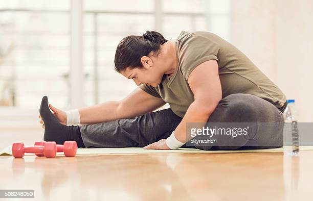 Fat woman stretching on the floor.