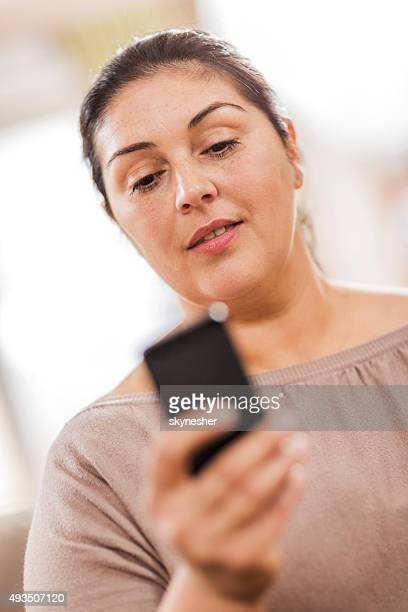 Fat woman text messaging on cell phone.