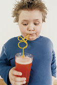 Fat Young Boy Drinking Cordial Through a Drinking Straw