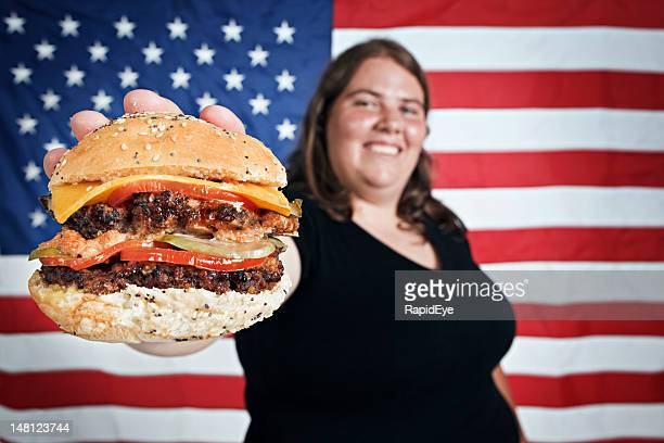 Fat Junge Frau smilingly bietet burger mit US-Flagge