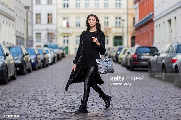 Fata Hasanovic wearing a black long fluffy jacket sassy classy black long shirt silver hand bag black leather pants and black heavy boots from sassy...