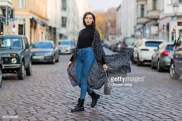 Fata Hasanovic wearing a black turtleneck high waisted blue denim jeans black NA KD coat with white dots black sassy classy heavy boots silver sassy...