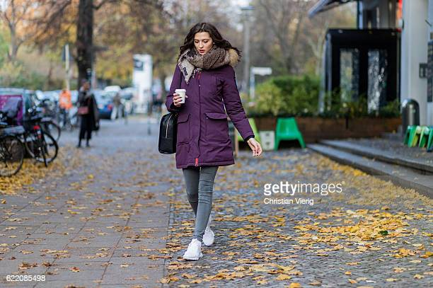Fata Hasanovic wearing a sassy classy scarf a purple brekka parka jacket with hooded fur grey skinny Dr Denim jeans white Nike sneaker black Asos bag...