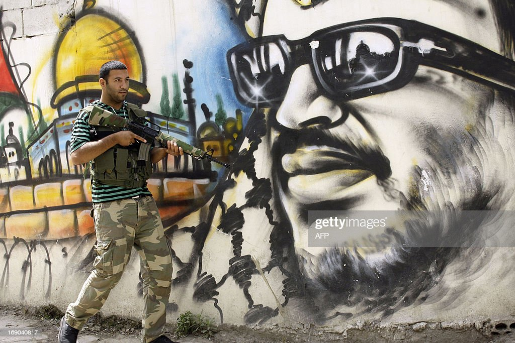 A Fatah movement member walks past a mural of the late Palestinian leader Yasser Arafat in the Ain al-Helweh Palestinian refugee camp on the outskirts of the southern Lebanese city of Sidon, on May 19, 2013, after clashes that erupted in the camp last night between Fatah and Islamist militants which left at least one killed and tens injured according to local news reports.
