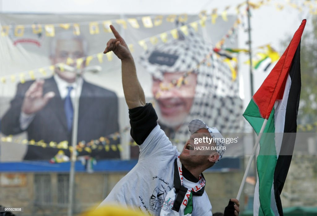 A Fatah supporter waves a national flag in front of a billboard bearing pictures of late Palestinian leader Yasser Arafat and his successor current...