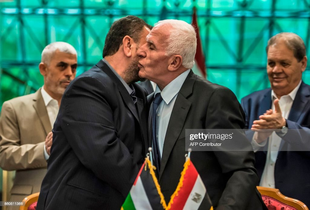 Fatah's Azzam al-Ahmad (R) and Saleh al-Aruri (L) of Hamas kiss after signing a reconciliation deal in Cairo on October 12, 2017, as the two rival Palestinian movements ended their decade-long split following negotiations overseen by Egypt. The new Hamas deputy leader and the head of Fatah's delegation struck the deal which was described by Palestinian Authority president Mahmud Abbas as a 'final agreement' to end their crippling division, which has at times erupted into deadly conflict over the past ten years. /