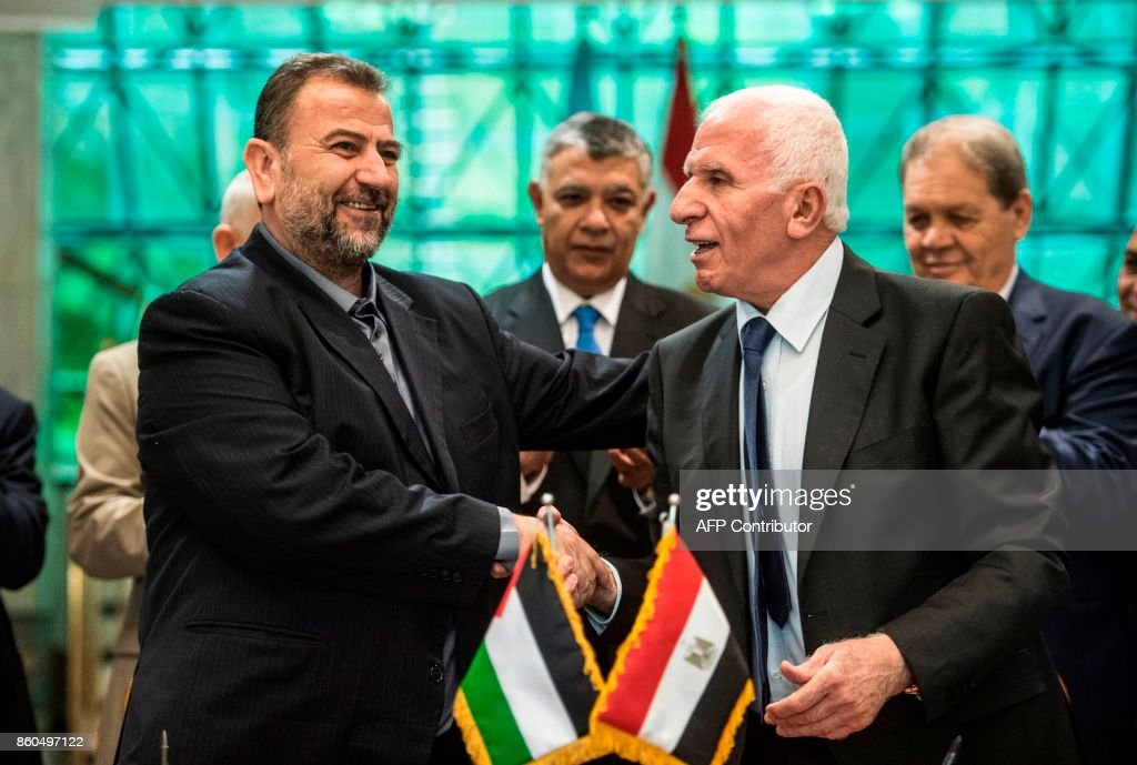 Fatah's Azzam al-Ahmad (R)and Saleh al-Aruri (L) of Hamas shake hands after signing a reconciliation deal in Cairo on October 12, 2017, as the two rival Palestinian movements ended their decade-long split following negotiations overseen by Egypt. The new Hamas deputy leader and the head of Fatah's delegation struck the deal which was described by Palestinian Authority president Mahmud Abbas as a 'final agreement' to end their crippling division, which has at times erupted into deadly conflict over the past ten years. /