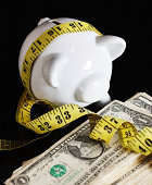 Fat-bellied piggybank wrapped in measuring tape eyes stack of do
