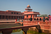 Fatehpur Sikri architecture with red stone and people with pond reflection Agra India