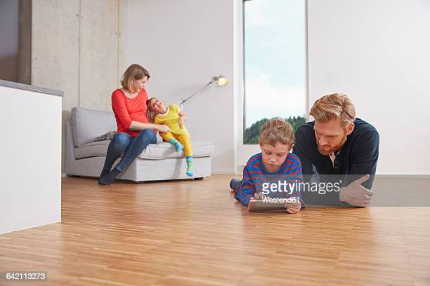 Fathar and son with digital tablet lying on floor