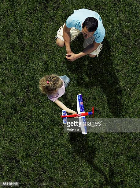 A father a daughter playing with a toy airplane