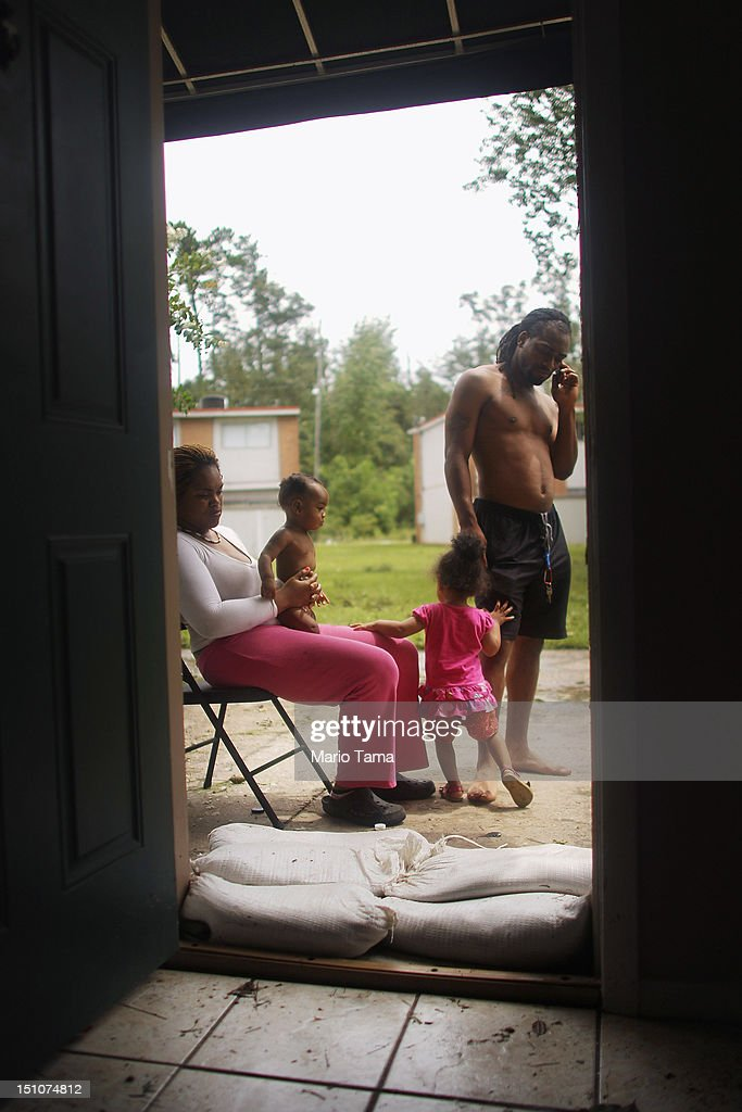 Father Aaron Cann, daughter Paris Cann, son Aaron Jr. and mother Dominique Lumar sit outside the sandbagged flooded apartment they had evacuated to from New Orleans on August 31, 2012 in Slidell, Louisiana. After evacuating to the Slidell apartment to stay with a family member, the Slidell apartment flooded yesterday morning and is now without power. The family's New Orleans home is also without power. Louisiana residents are coping with the aftermath of Hurricane Isaac with ongoing flooding, destroyed property and many still without electricity.