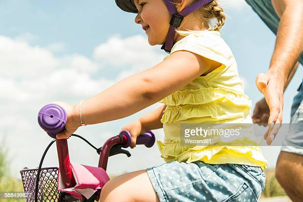 Father accompanying daughter on bike
