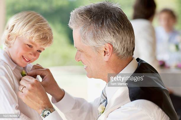 Father adjusting sons tie at party