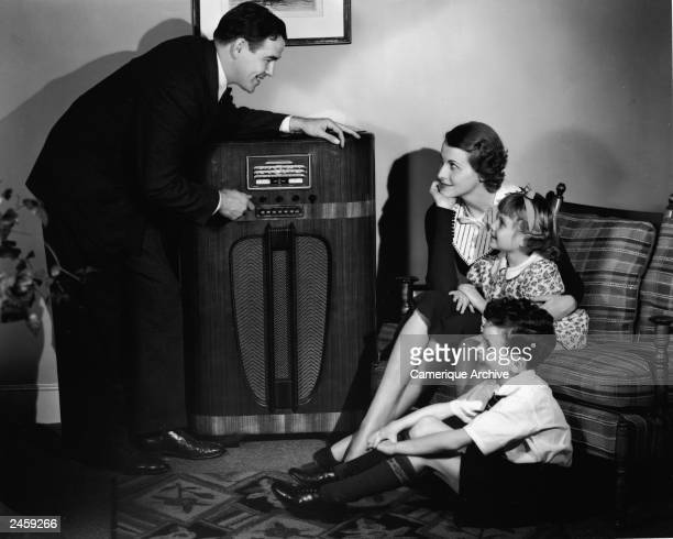 A father adjusts the tuning dial on a radio console as his family sits and listens in their living room 1930s