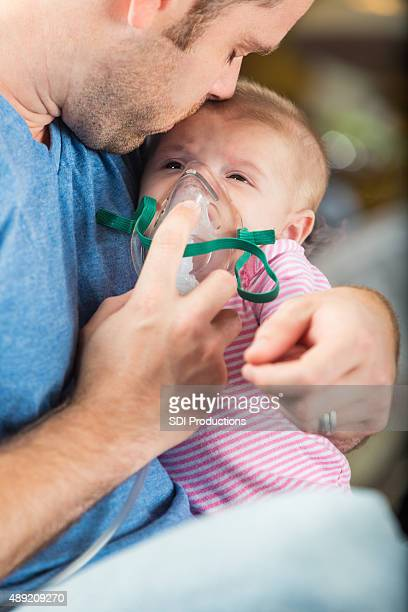 Father admistering breathing treatment to infant daughter with cystic fibrosis