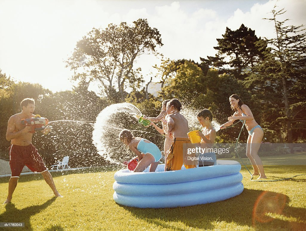 Father Aims a Water Gun at Children Throwing Water in a Paddling Pool : Stock Photo